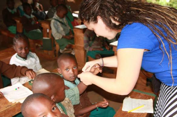 Maya tying the bracelets on the kids. Natalie read the story of how Jesus is our friend.